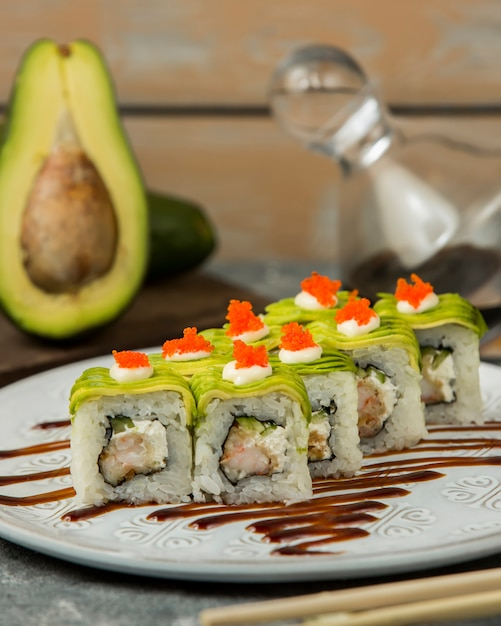 Close up of sushi rolls with shrimp, cucumber covered with avocado Free Photo