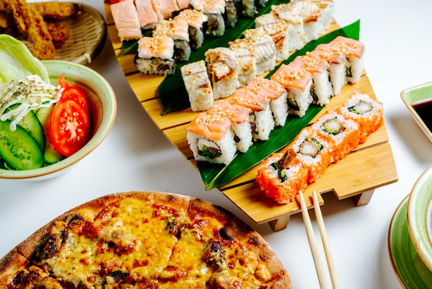 Close up of sushi set next to pizza and salad Free Photo