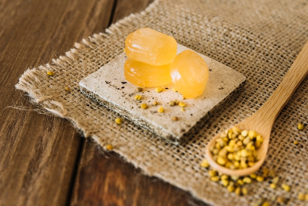 Close-up of sweet candies and bee pollen seeds on sack cloth Free Photo