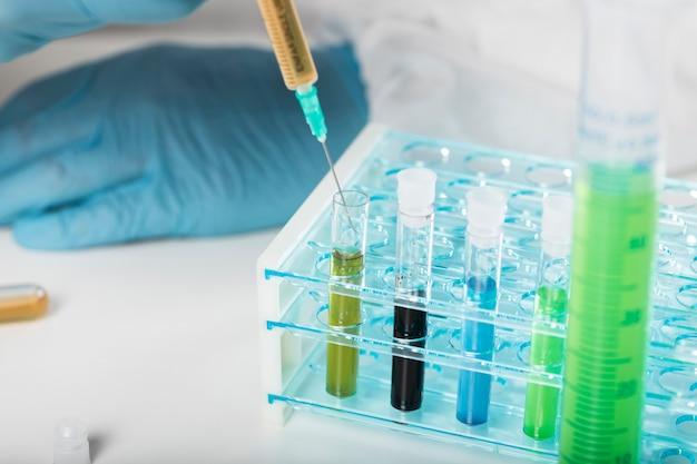 Close-up syringe taking medical samples Free Photo
