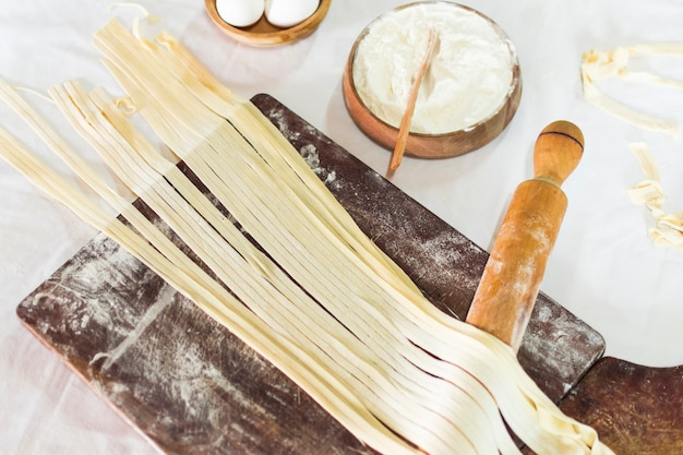 Close-up of tagliatelle pasta on wooden board with flour and rolling pins Free Photo