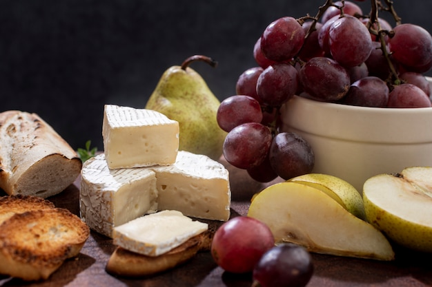 Close-up tasty brie cheese and grapes Free Photo