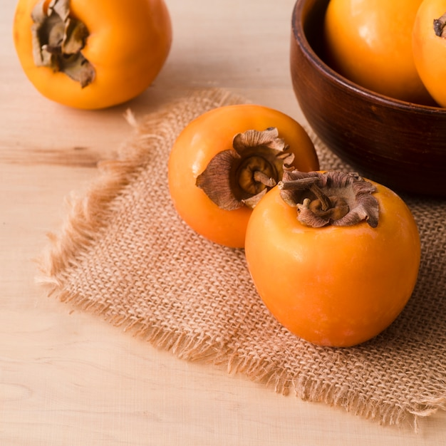Close-up tasty persimmons on the table Free Photo
