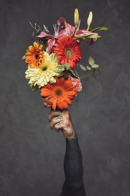 Close-up of tattooed young man holding floral bouquet in hand against grey wall Free Photo