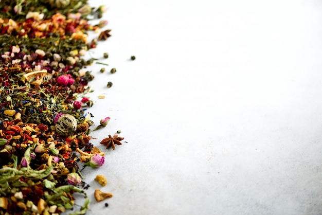 Close up tea background: green, black, floral, herbal, mint, melissa, ginger, apple, rose, lime tree, fruits, orange, hibiscus, raspberry, cornflower, cranberry. Premium Photo