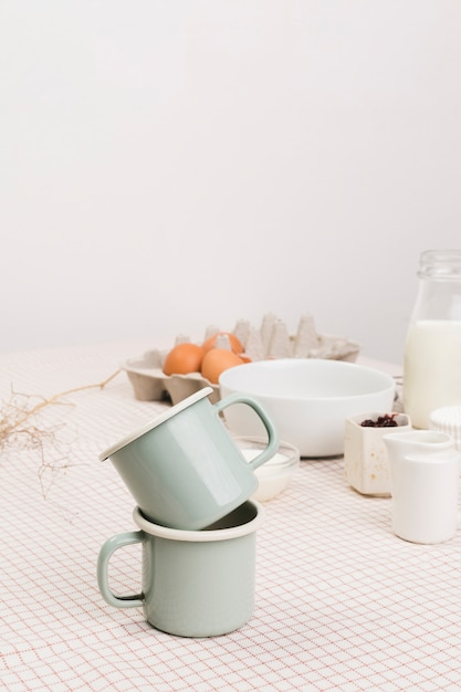 Close-up of tea mugs in front of organic ingredients over table Free Photo