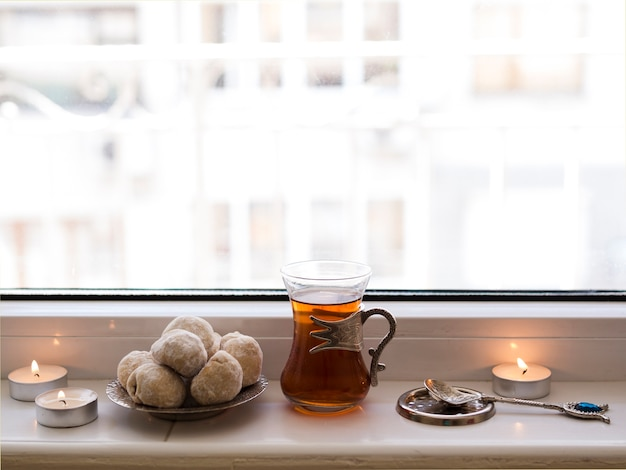 Close up tea and nastar sitting on window sill Free Photo