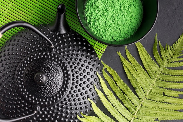 Close-up of teapot with green match tea powder and fern leaves Free Photo