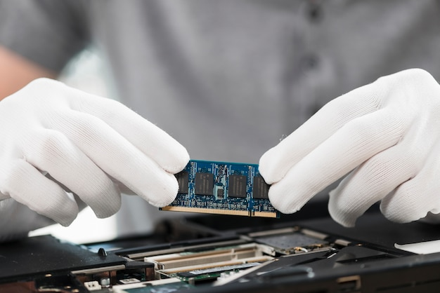 Close-up of a technician holding computer chip Free Photo