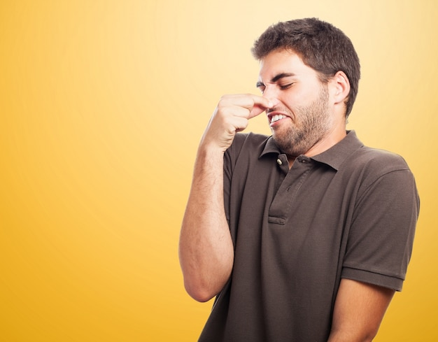 Close-up of teen with brown t-shirt holding his nose Free Photo