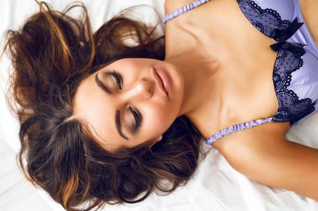 Chiuda sul ritratto di modo tenero di bella ragazza con capelli lunghi perfetti e trucco naturale, posa sul letto in reggiseno di seta alla moda. atmosfera romantica mattutina. Foto Gratuite