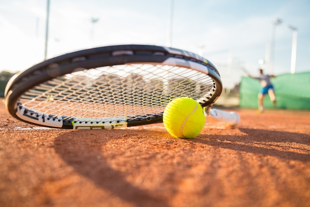 Close-up tennis racket and ball placed on court ground while player hitting ball. Premium Photo