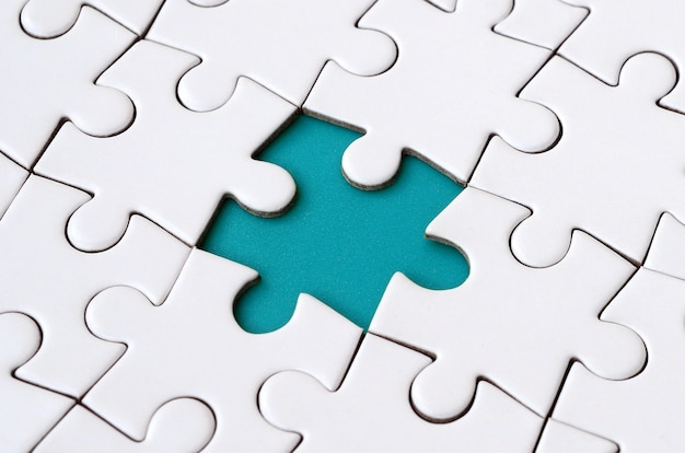 Close-up texture of a white jigsaw puzzle in assembled state with missing elements forming a blue pad for text. Premium Photo