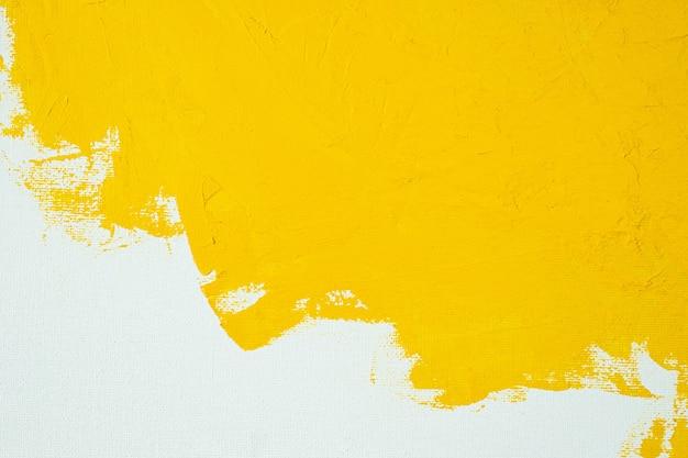 白い色のキャンバスブラシマークストローク背景にテクスチャイエロー色のペンキを閉じる Premium写真