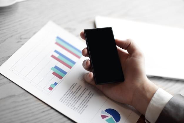 닫기 Up.the 사업가 자신의 스마트 폰을 사용하여 재무 Data.business 개념을 확인 프리미엄 사진