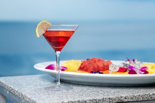 クローズアップ:カクテルはコスモポリタンでレモンのスライスがあり、その隣にはエキゾチックなフルーツが入ったプレートがあります:スイカ、パイナップル、ドラゴンフルーツ。ビーチパーティー。プールパーティー。 Premium写真