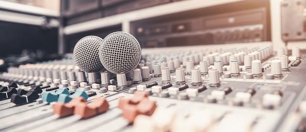 Крупный план микрофона размещен на профессиональном аудио микшере в студии. Premium Фотографии