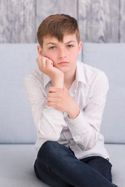 Primo piano di un ragazzo pensieroso, seduto sul divano guardando la fotocamera Foto Gratuite