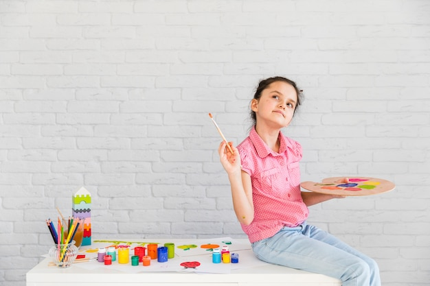 Close-up of a thoughtful girl sitting on white table holding paintbrush and palette Free Photo