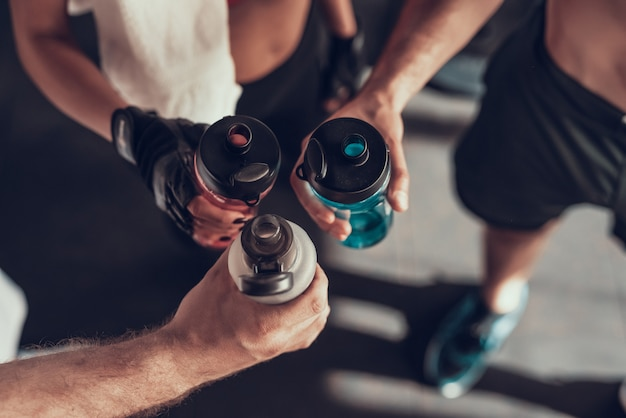 Close up. three hands with bottles in the gym. Premium Photo