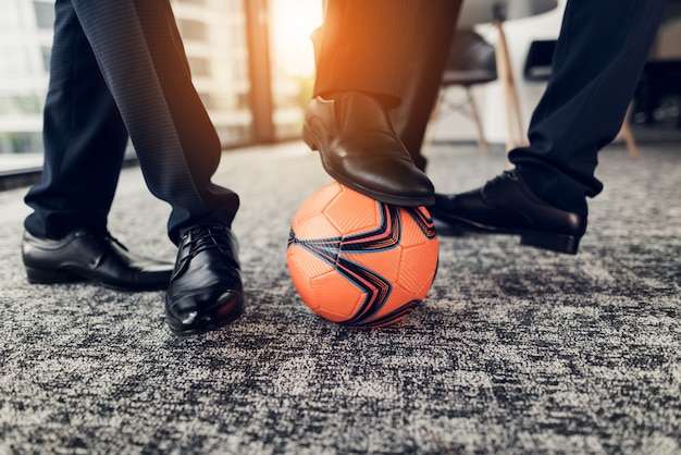 Close up  three men in black shoes play an orange ball Premium Photo