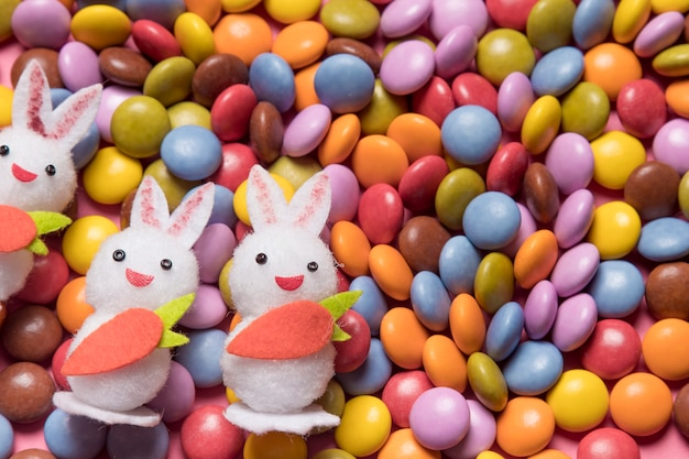 Close-up of three white bunnies over the colorful gem candies Free Photo