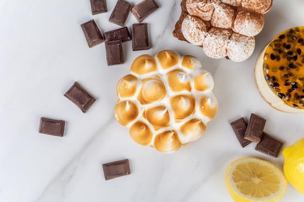 おいしいミニチョコレート、レモンパイ、パッションフルーツケーキのクローズアップ。コンセプトを調理します。 無料写真