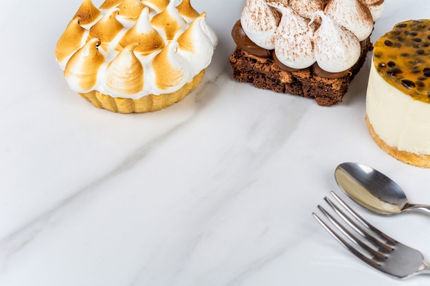 おいしいミニチョコレート、レモンパイ、パッションフルーツケーキのクローズアップ。クックのコンセプト。 無料写真