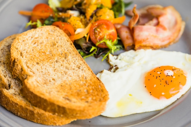 Close-up of toast; fried eggs; salad and bacon on gray ceramic plate Free Photo