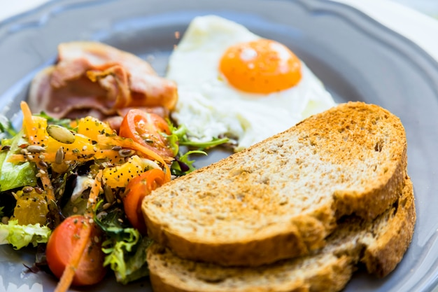 Close-up of toast; fried eggs; salad and bacon served on ceramic plate Free Photo