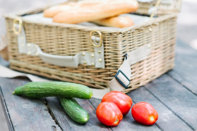 Close up of tomatoes and cucumbers over wooden table in front of an open picnic basket. Premium Photo