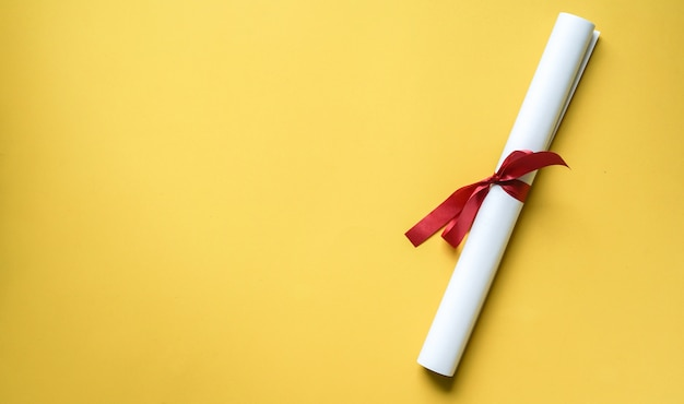 Close up top view of certificated degree on yellow background Premium Photo