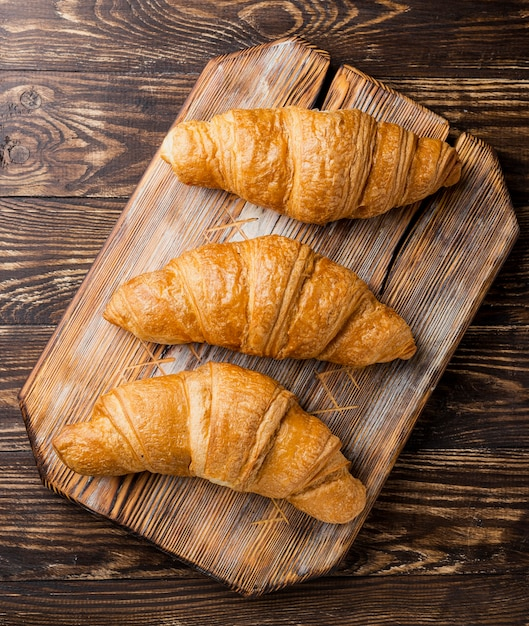 Close-up top view delicious baked croissants on wooden board Free Photo