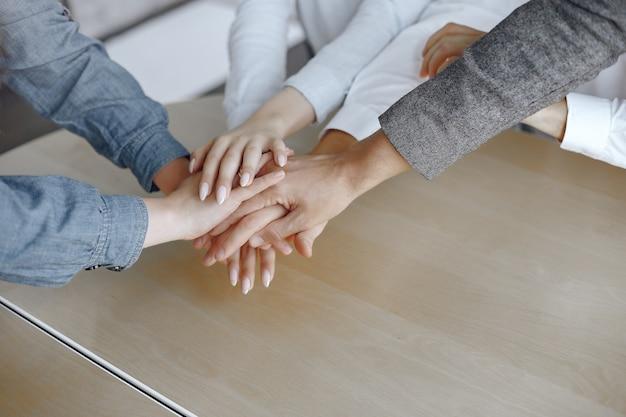 젊은 기업들의 상위 뷰를 닫습니다. 손을 모으는 팀. 손의 스택. 화합과 팀워크 개념. 무료 사진