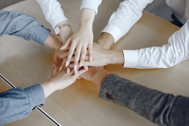 Закройте вверх по взгляду молодых деловых людей. команда складывает руки. стек рук. концепция единства и совместной работы. Бесплатные Фотографии
