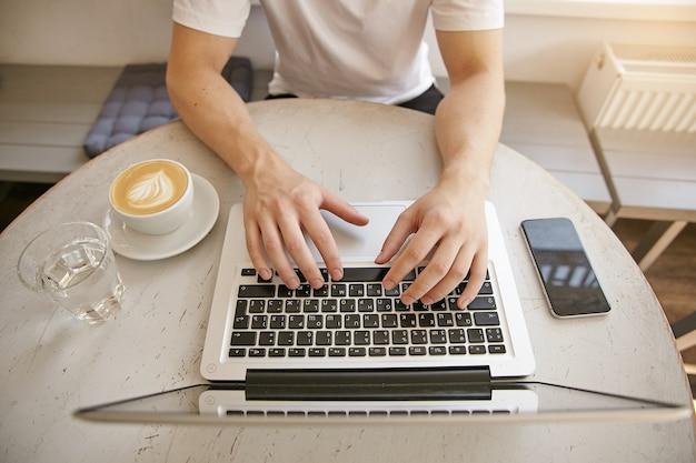 コーヒー、最新のラップトップ、スマートフォンを備えた白いデスクトップのクローズアップ上面図。白いtシャツを着た青年実業家がシティカフェで在宅勤務 無料写真