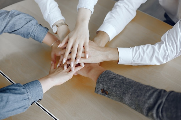 Close up top view of young business people. team putting their hands together. stack of hands. unity and teamwork concept. Free Photo