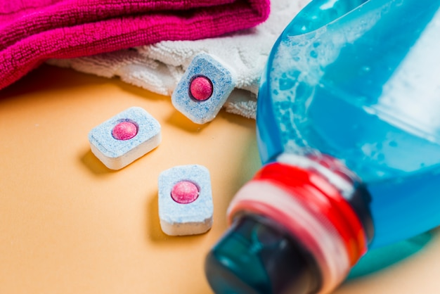 Close-up of towels and liquid detergent with three dishwasher tablets Free Photo