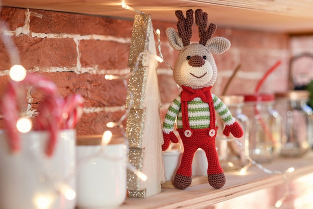 Close up toy amigurumi deer in striped sweater and stylish red butterfly tie stands on the wooden shelf near the decorated christmas tree and christmas lights. Premium Photo