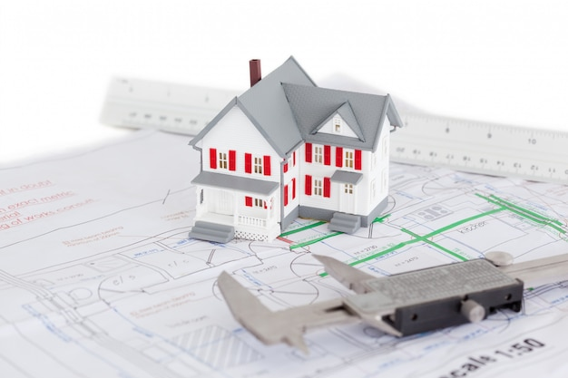 Close-up of toy house model and caliper on a plan Premium Photo