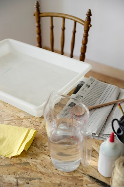 Close-up of a tray and jar filled with water on desk Free Photo