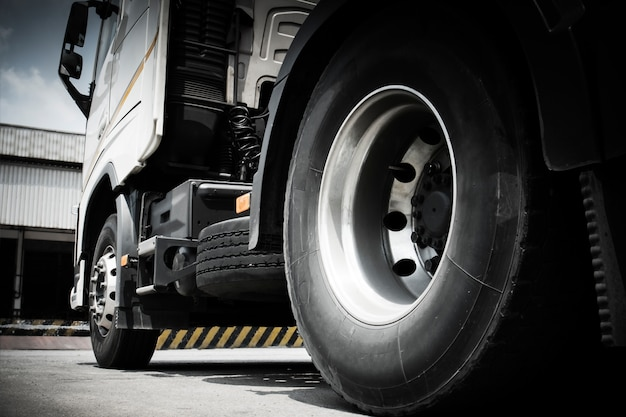 Close up the truck wheels of semi truck parking at warehouse Premium Photo
