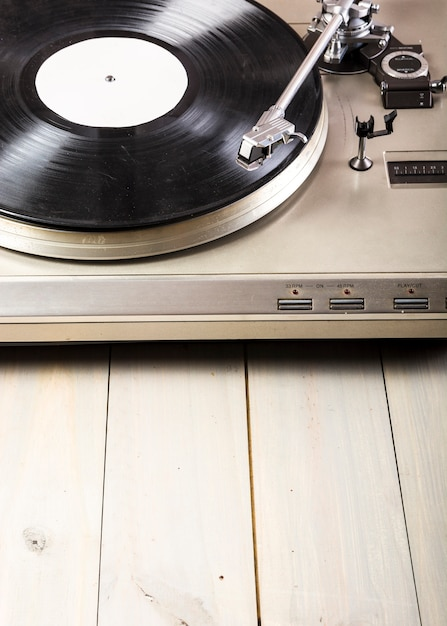 Close-up of turntable vinyl record player on wooden table Free Photo