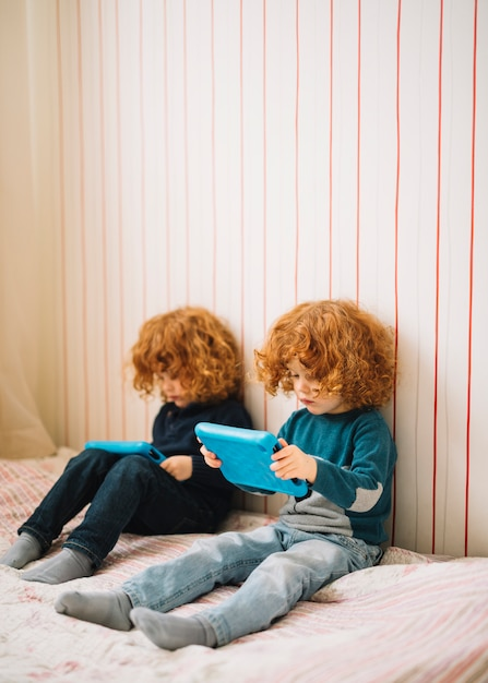 Close-up of twins with red headed hair looking at digital tablet Free Photo