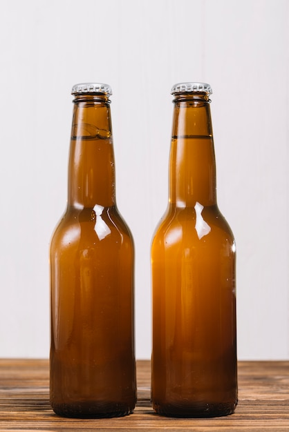 Close-up of two beer bottles on wooden surface Free Photo