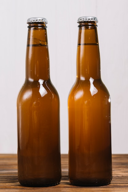 Close-up of two beer bottles on wooden table top Free Photo
