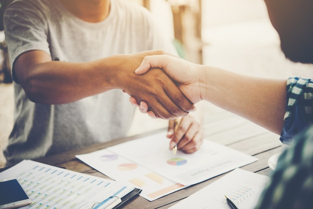 Close-up of two business people shaking hands while sitting at the working place. Free Photo