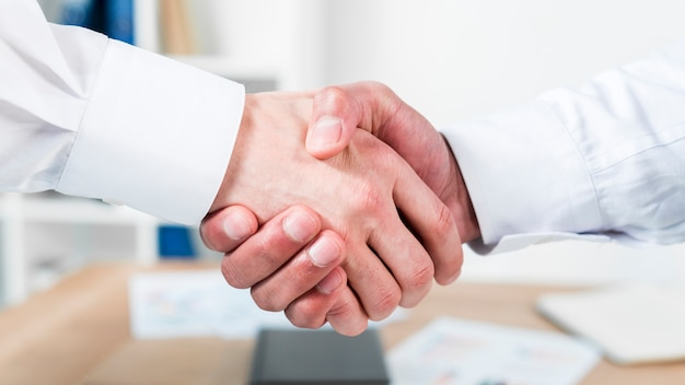 Close-up of two businessman shaking hands Free Photo