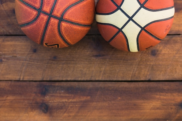 Close-up of two different type of basketball on wooden table Free Photo