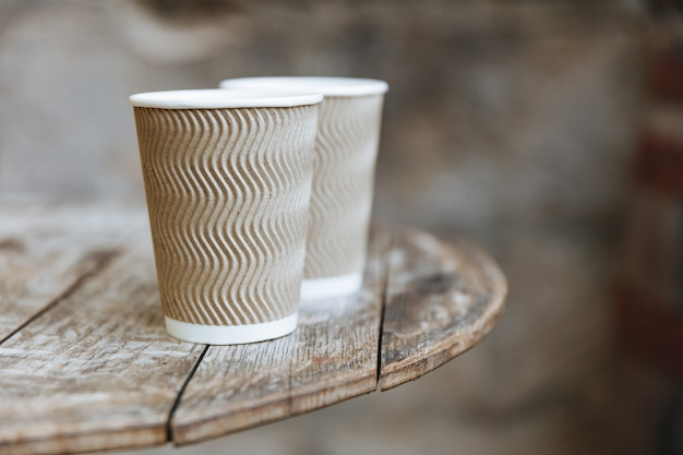 Close up of two disposable brown cups of hot flavored coffee Premium Photo